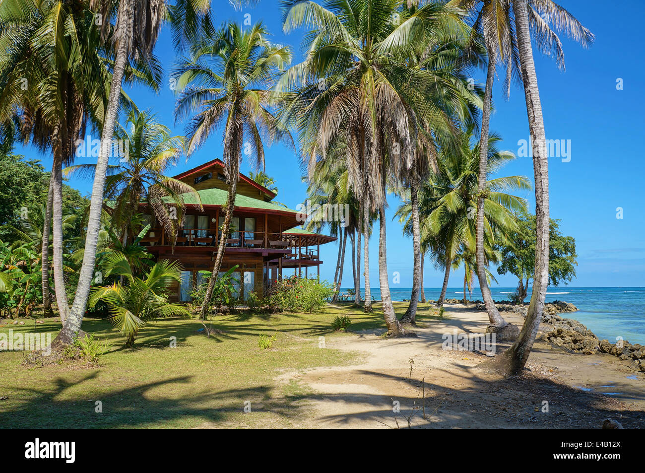Tropical beach house with coconut palm trees on an island in the Caribbean - Stock Image