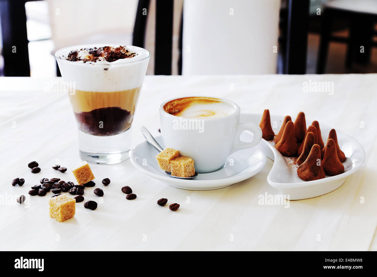 coffee and sweat candies on white table - Stock Image
