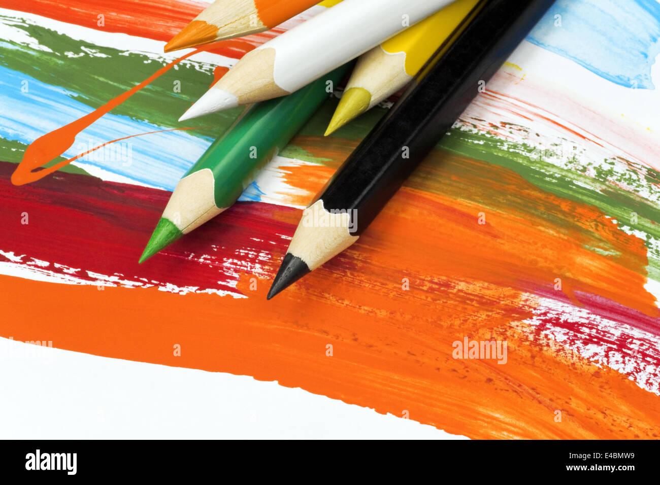 multi colored pencils on funny painted paper Stock Photo