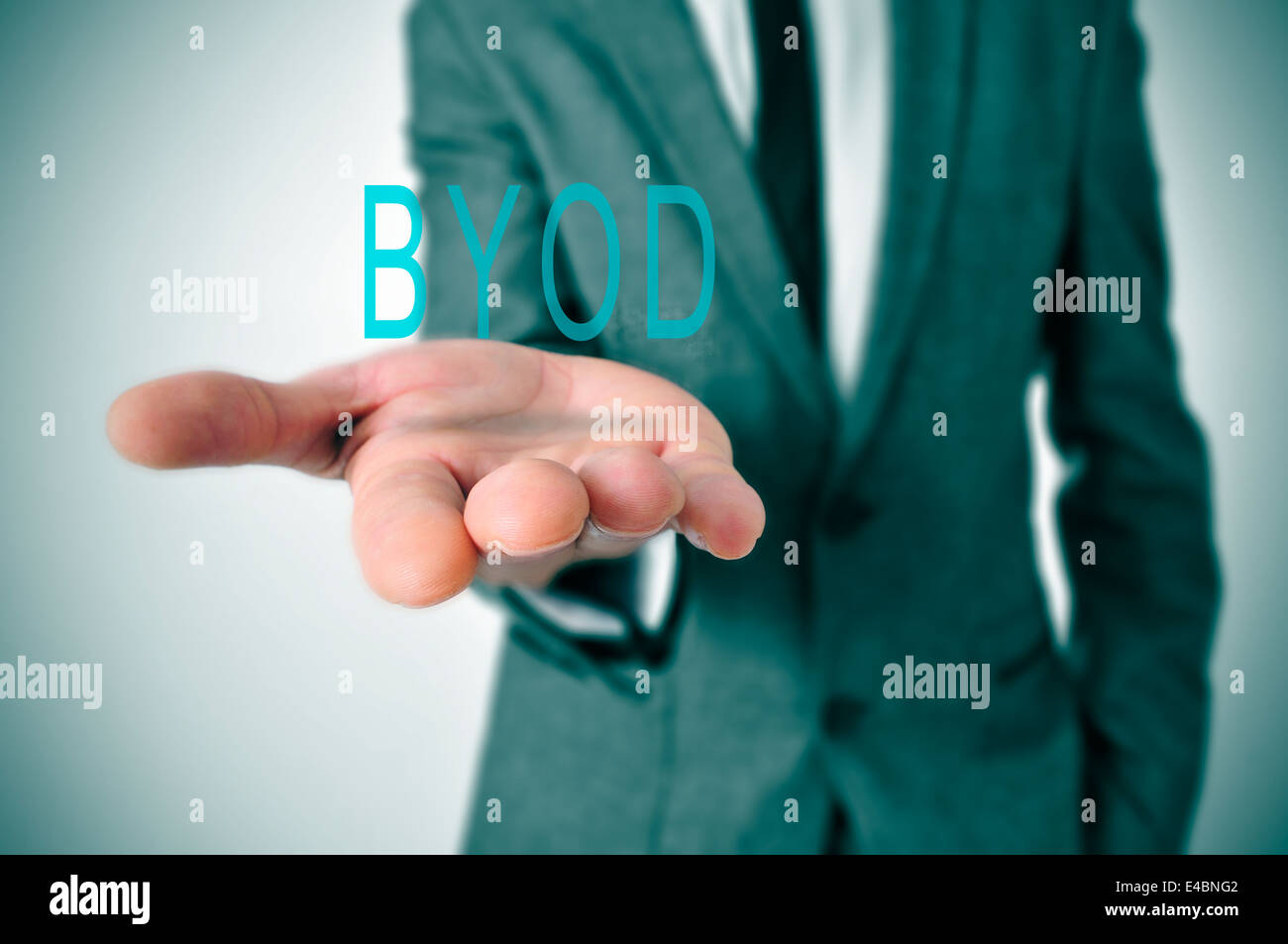 a man wearing a suit with the word BYOD, acronym for bring your own device, in his hand - Stock Image
