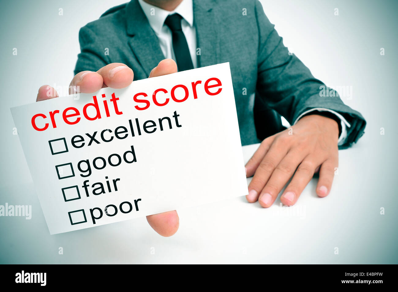 man in suit showing a signboard with the different ranges of the credit score: excellent, good, fair and poor - Stock Image