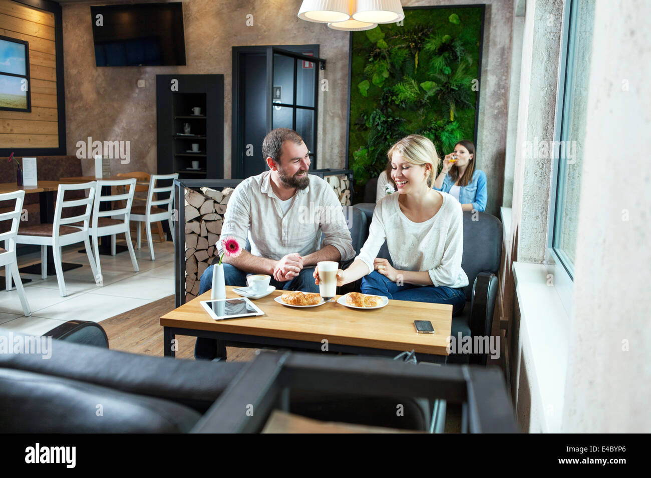 Couple flirting in a cafe, people in background - Stock Image