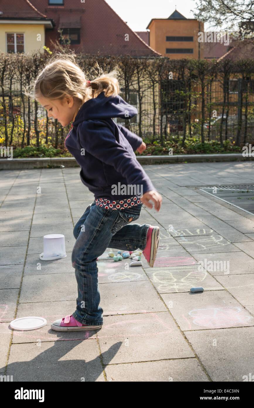 Blonde girl playing hopscotch on sidewalk, Munich, Bavaria, Germany - Stock Image