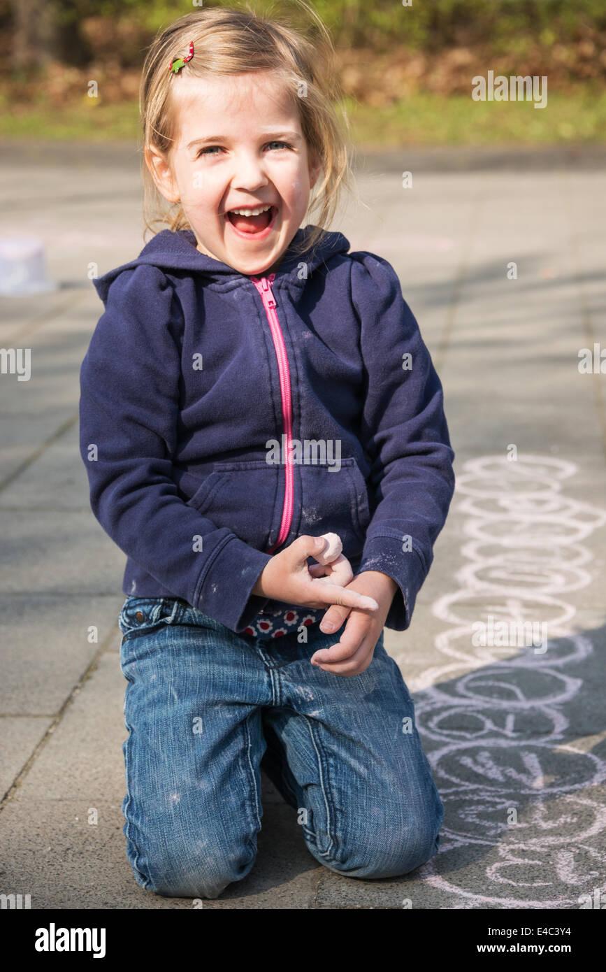 Blonde girl drawing with chalk on sidewalk, Munich, Bavaria, Germany - Stock Image