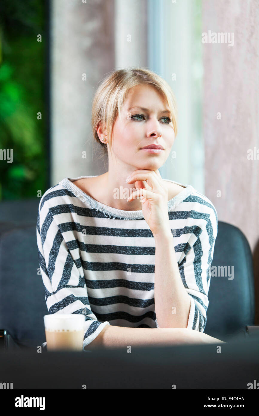Mid adult woman in striped shirt sits in cafe musing - Stock Image