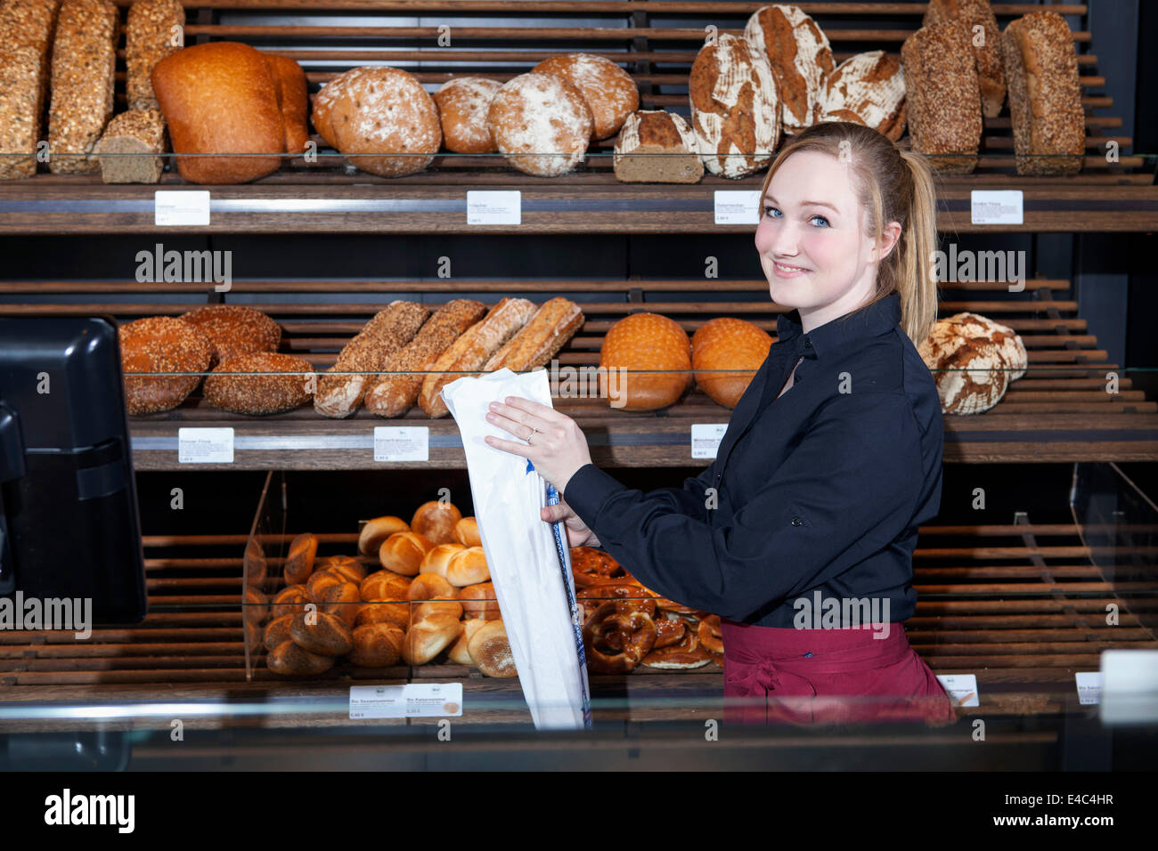 Female shop assistant in bakery packing bread into bag - Stock Image