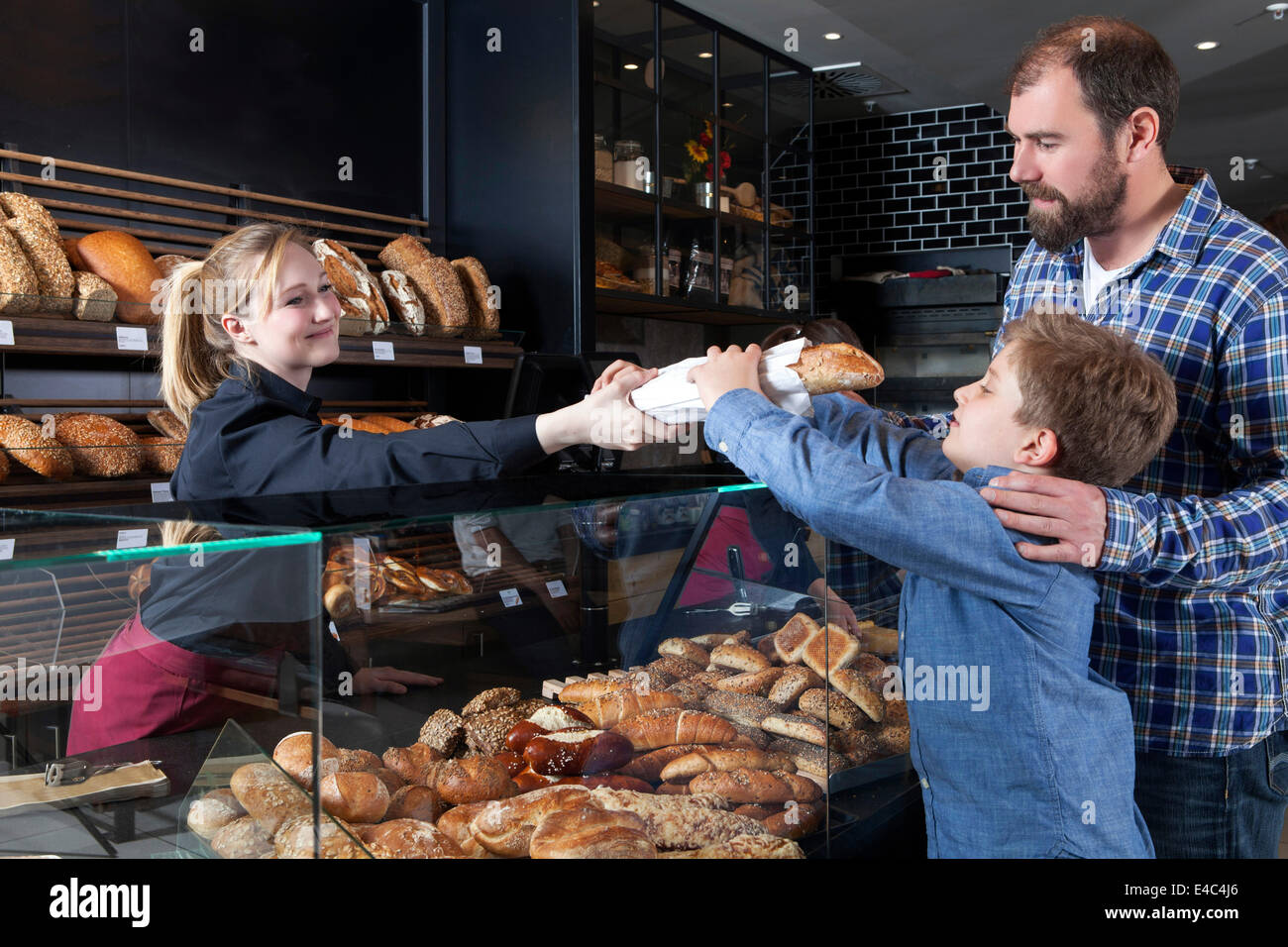 Father and son buying bread in a bakery - Stock Image