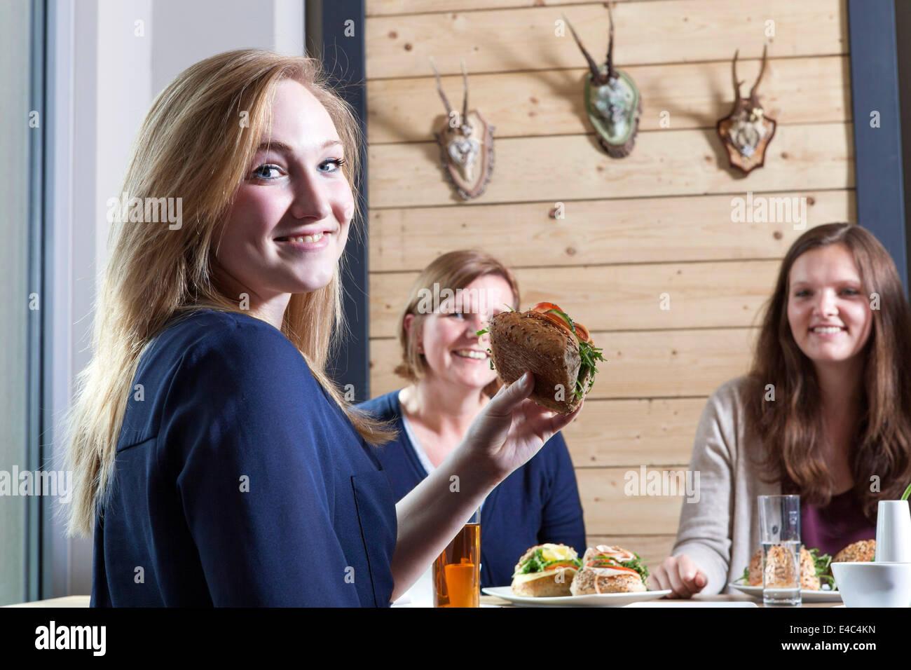 Three women having breakfast in a cafe - Stock Image