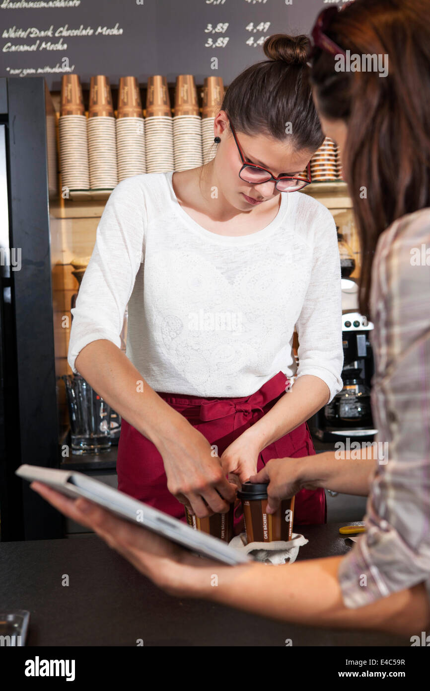 Two waitresses in a coffee shop preparing coffee to go - Stock Image