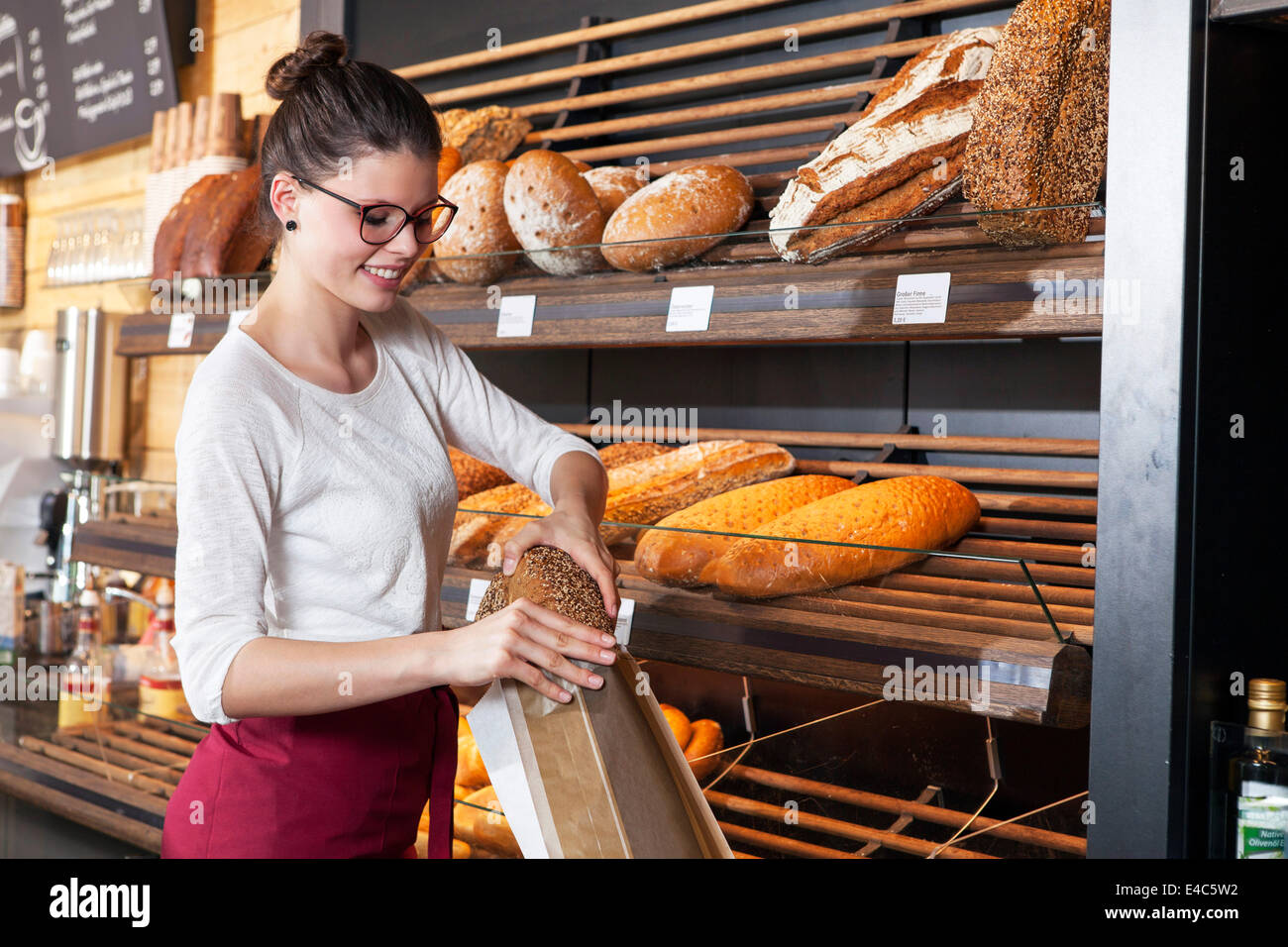 Shop assistant in bakery packing bread into a bag - Stock Image
