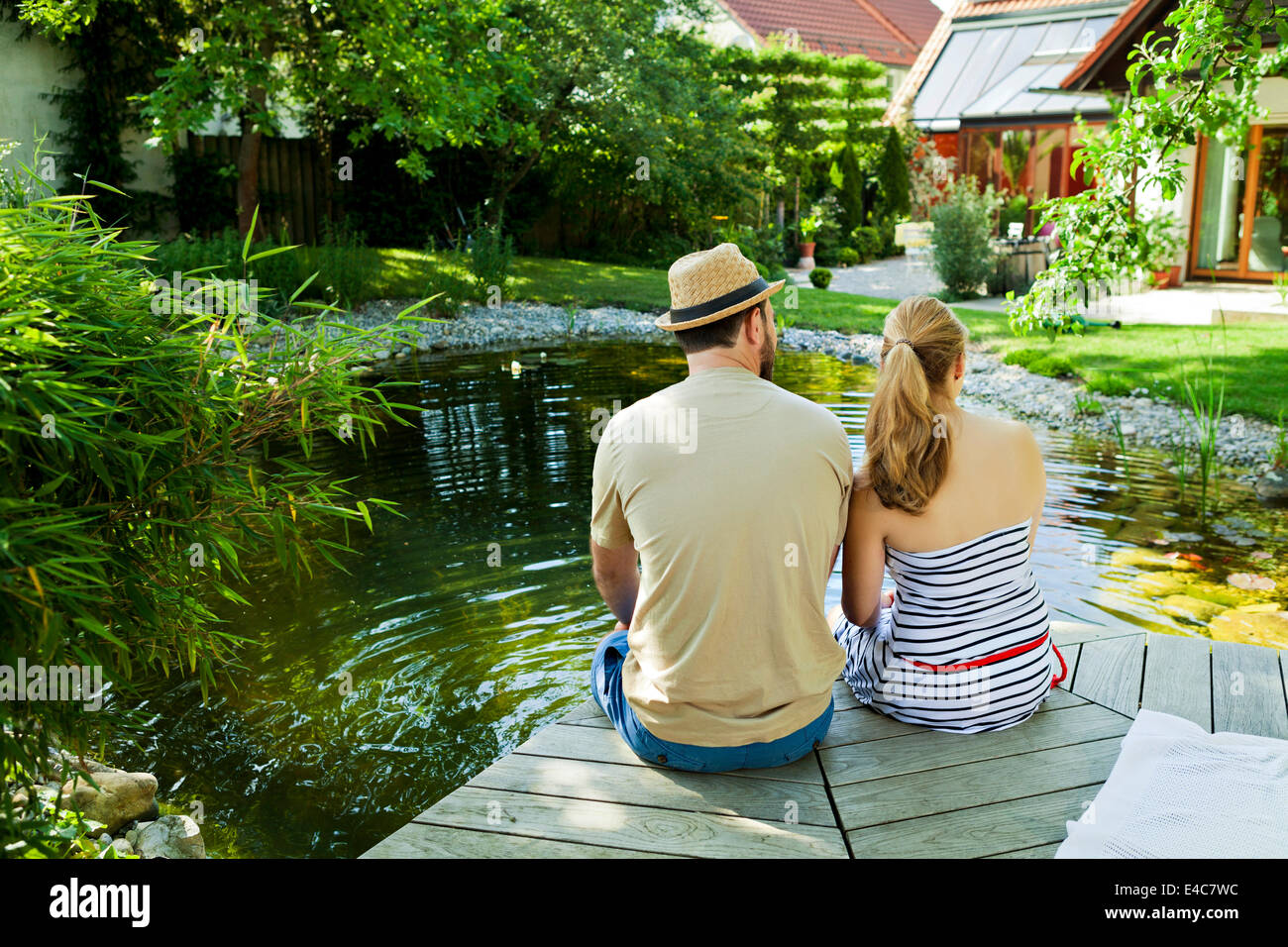 Heterosexual couple takes a break by the pond, rear view, Munich, Bavaria, Germany - Stock Image
