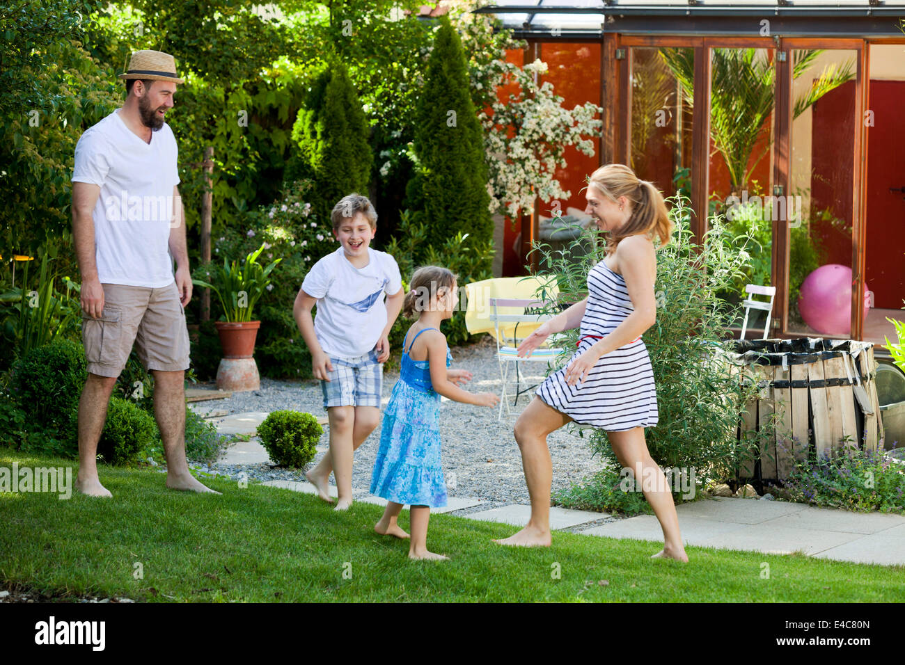 Family with two children in the garden fooling around, Munich, Bavaria, Germany - Stock Image