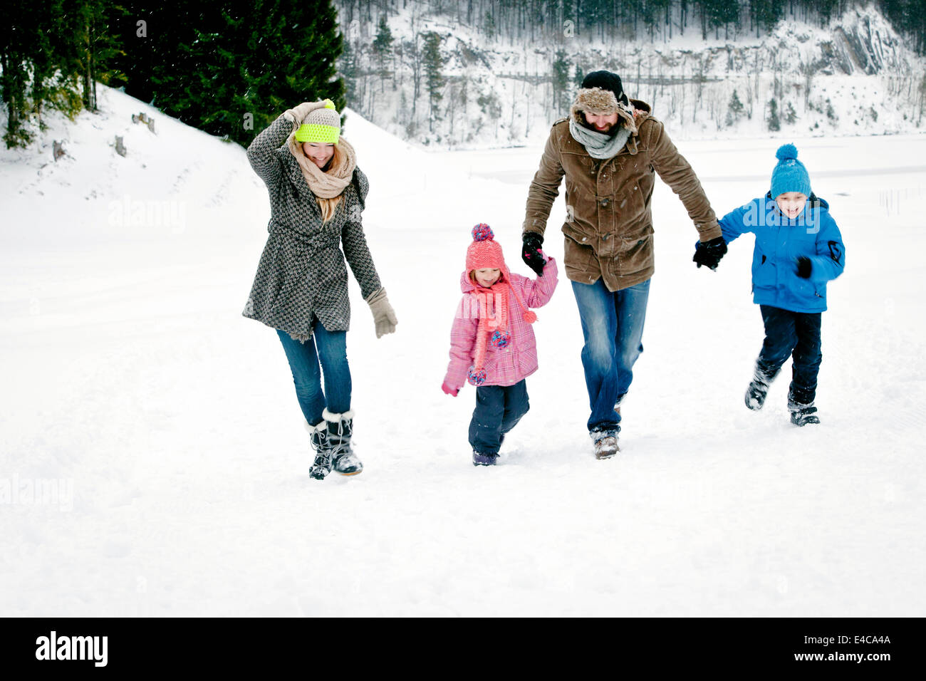 Family with two children in snow-covered landscape having fun, Bavaria, Germany - Stock Image