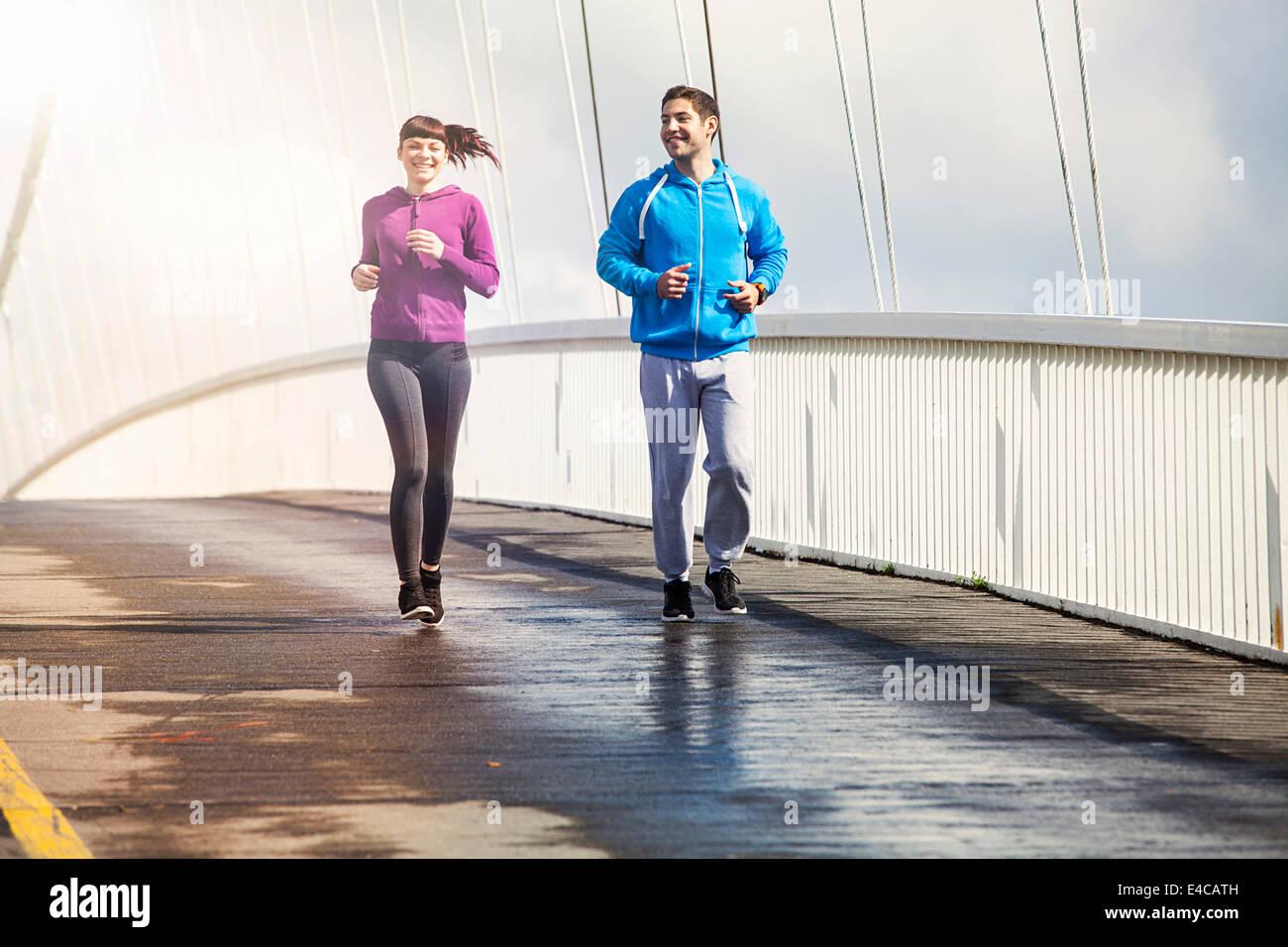 Young couple running on bridge, Osijek, Croatia - Stock Image