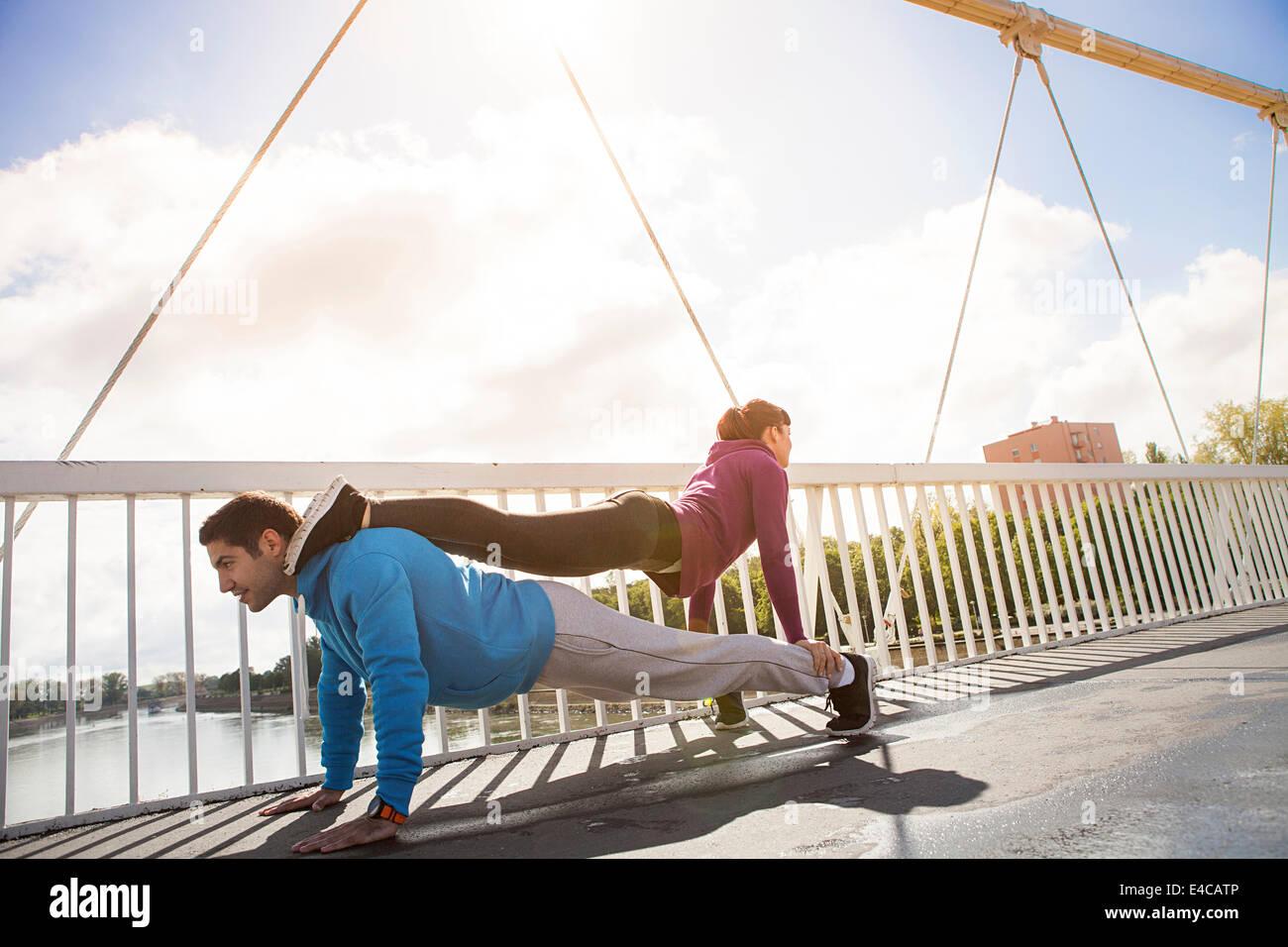 Young couple performing push-ups, man backing woman, Osijek, Croatia Stock Photo