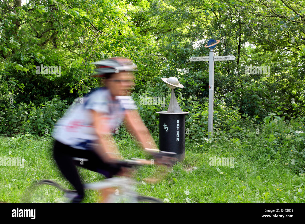 A cyclist passes a model of the planet Saturn on the York to Selby solar cycle path. - Stock Image