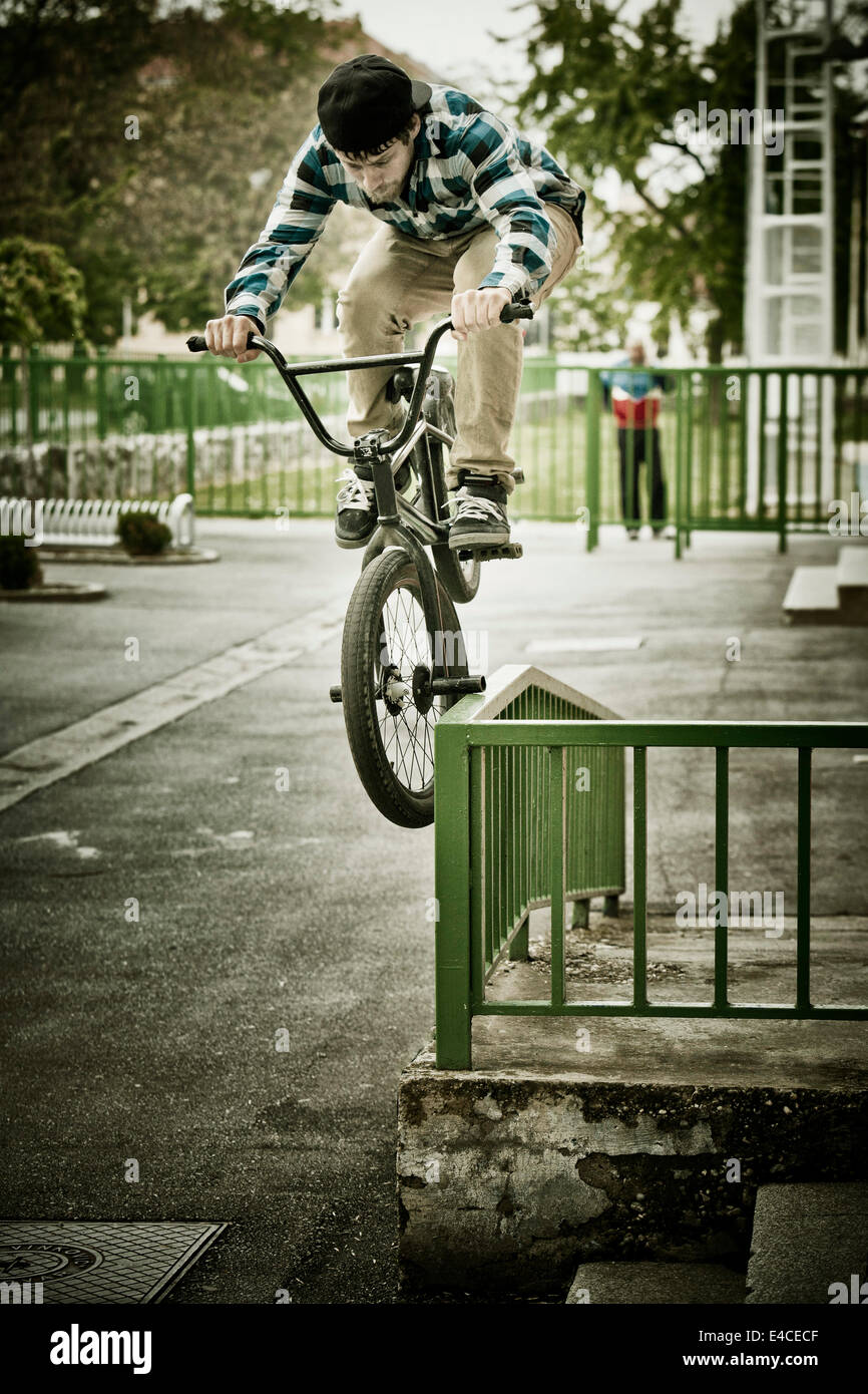 BMX biker performs a stunt on a railing - Stock Image