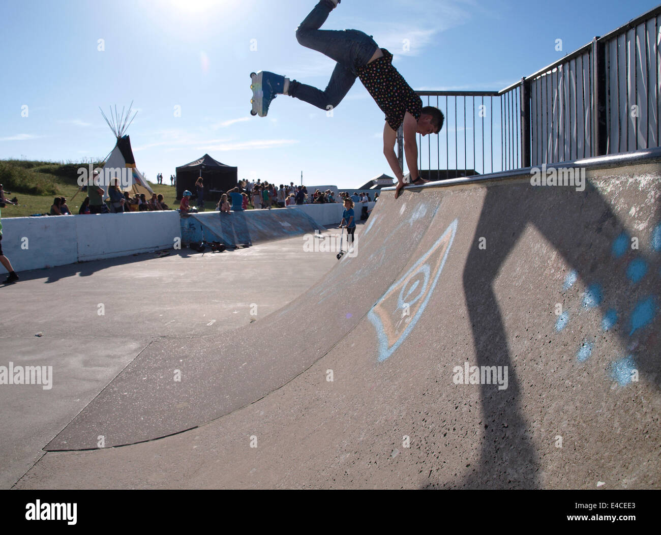 Teenager with inline skates on a half-pipe at Bude skatepark, Cornwall, UK - Stock Image