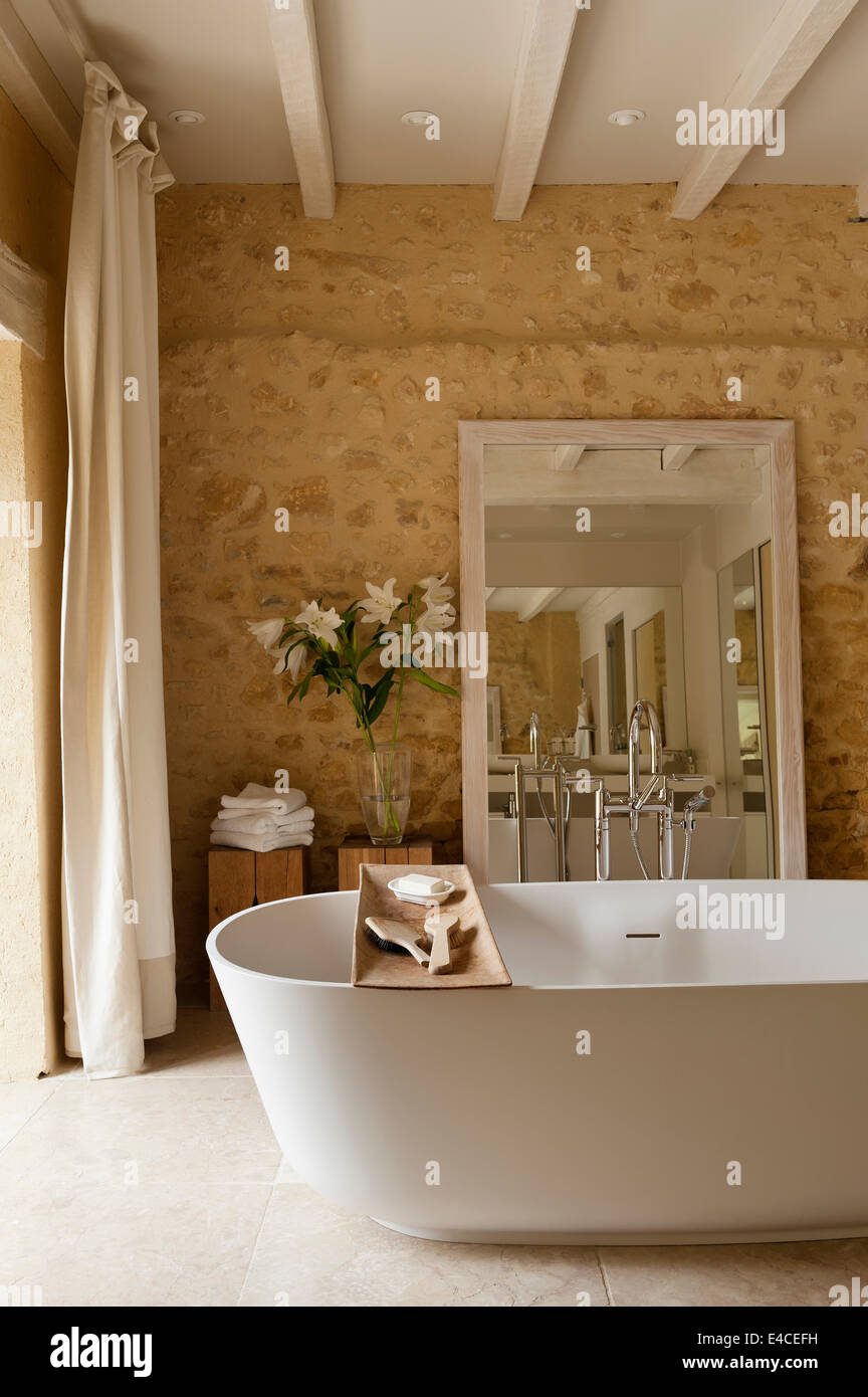 A Deep VAS 910 bath from Agape in bathroom with rough stone walls ...