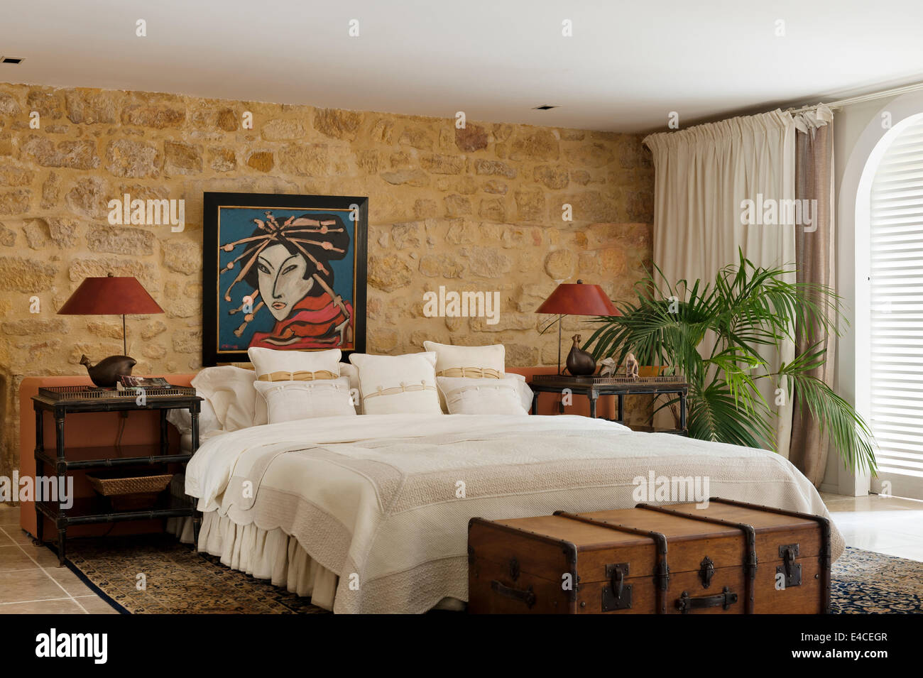 Stone walled bedroom with Geisha painting by Gillian Meijer, lacquer bedside tables and large wooden trunk - Stock Image