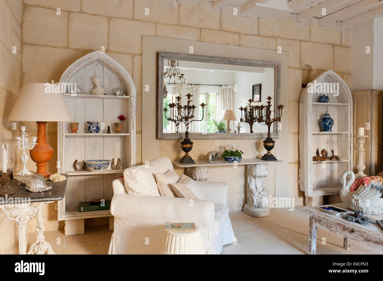 Pair of arched wooden shelves in sitting room with acanthus legged console table and candelabra. The walls are limestone blocks Stock Photo