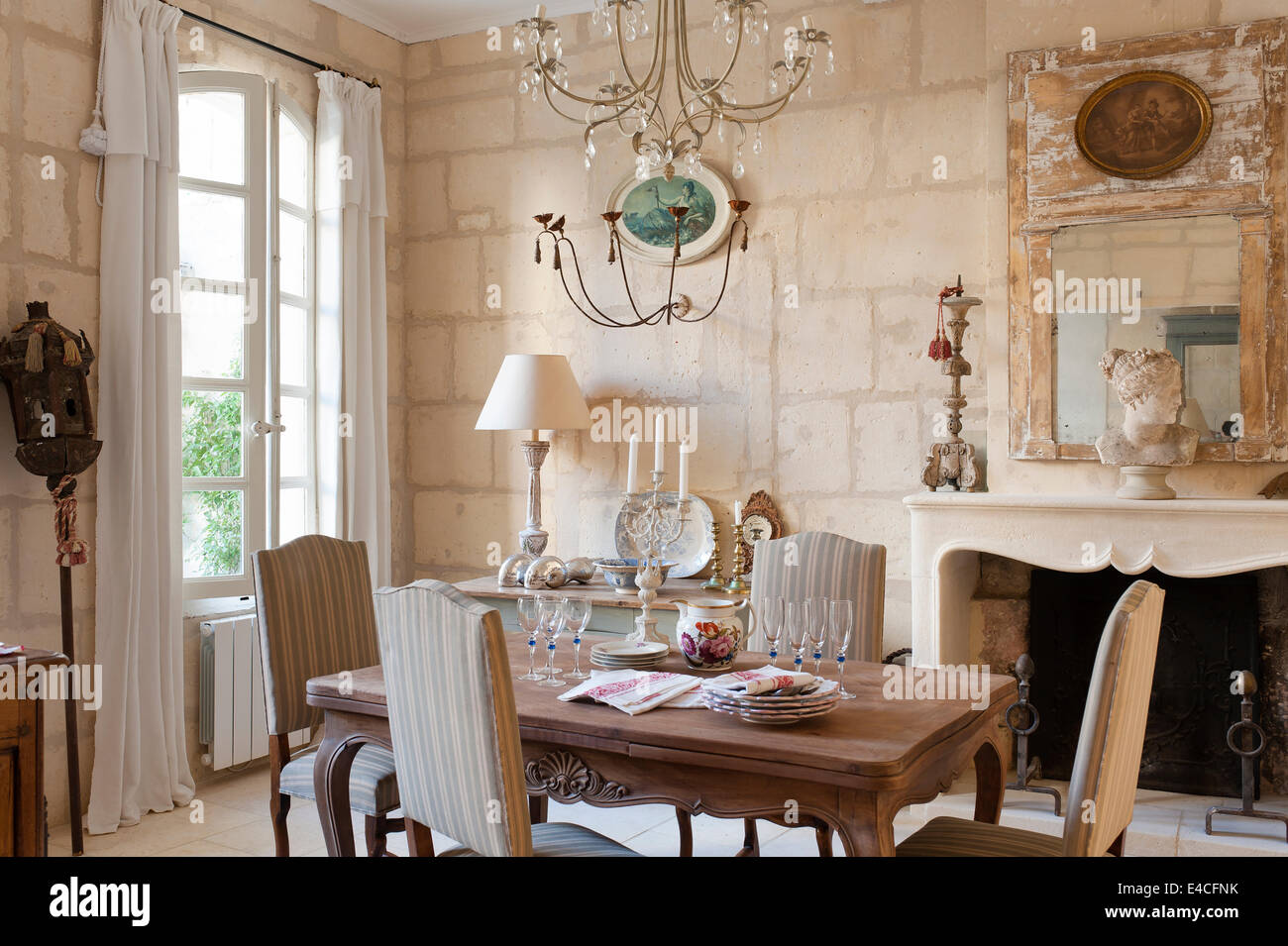 Wooden Dining Table With Upholstered Dining Chairs In Room With Stone  Fireplace And Limestone Block Walls