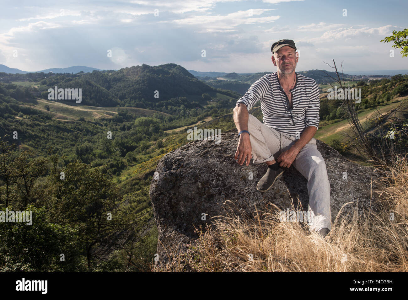 serious man sitting on rock wearing stripy top and cap in countryside looking directly at camera - Stock Image