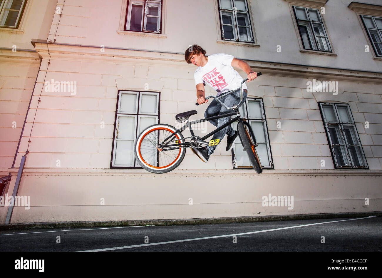 BMX biker performing a stunt in front of a house - Stock Image