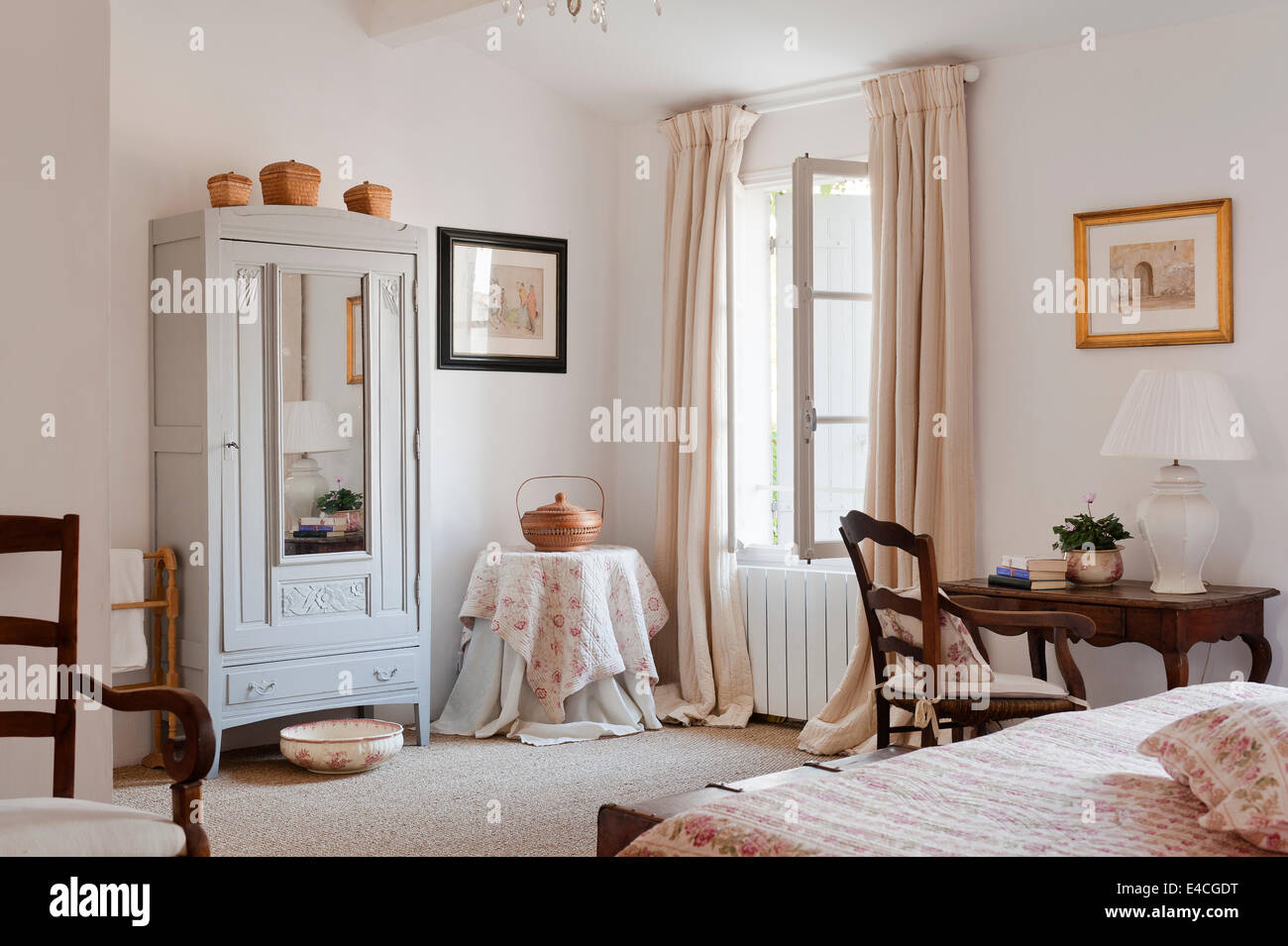 French cupboard in bedroom with seagrass mat and quilted floral fabric - Stock Image