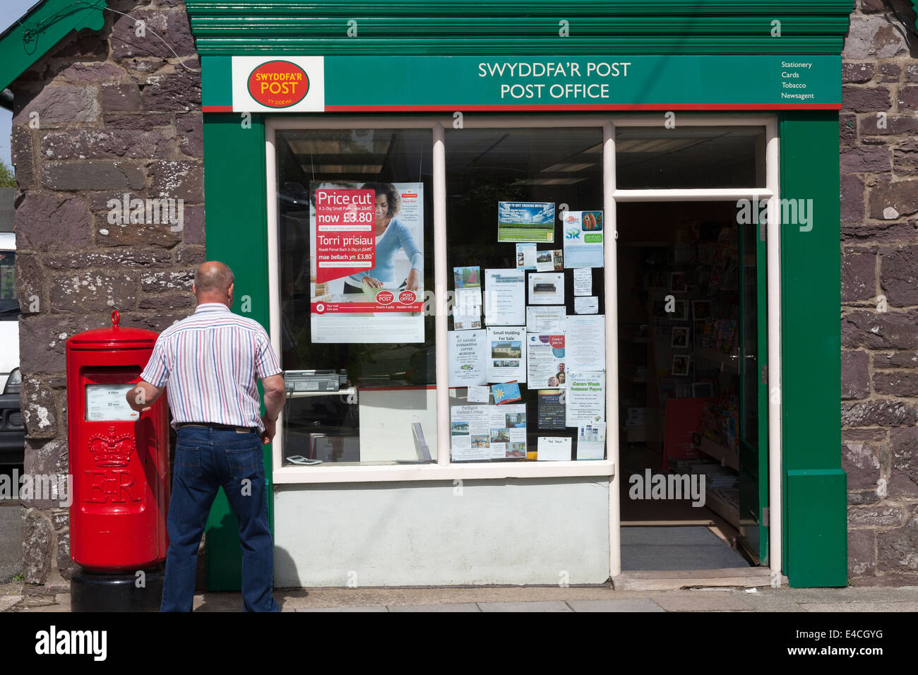 Man posting letter outside the Post Office, St Davids, Pembrokeshire - Stock Image