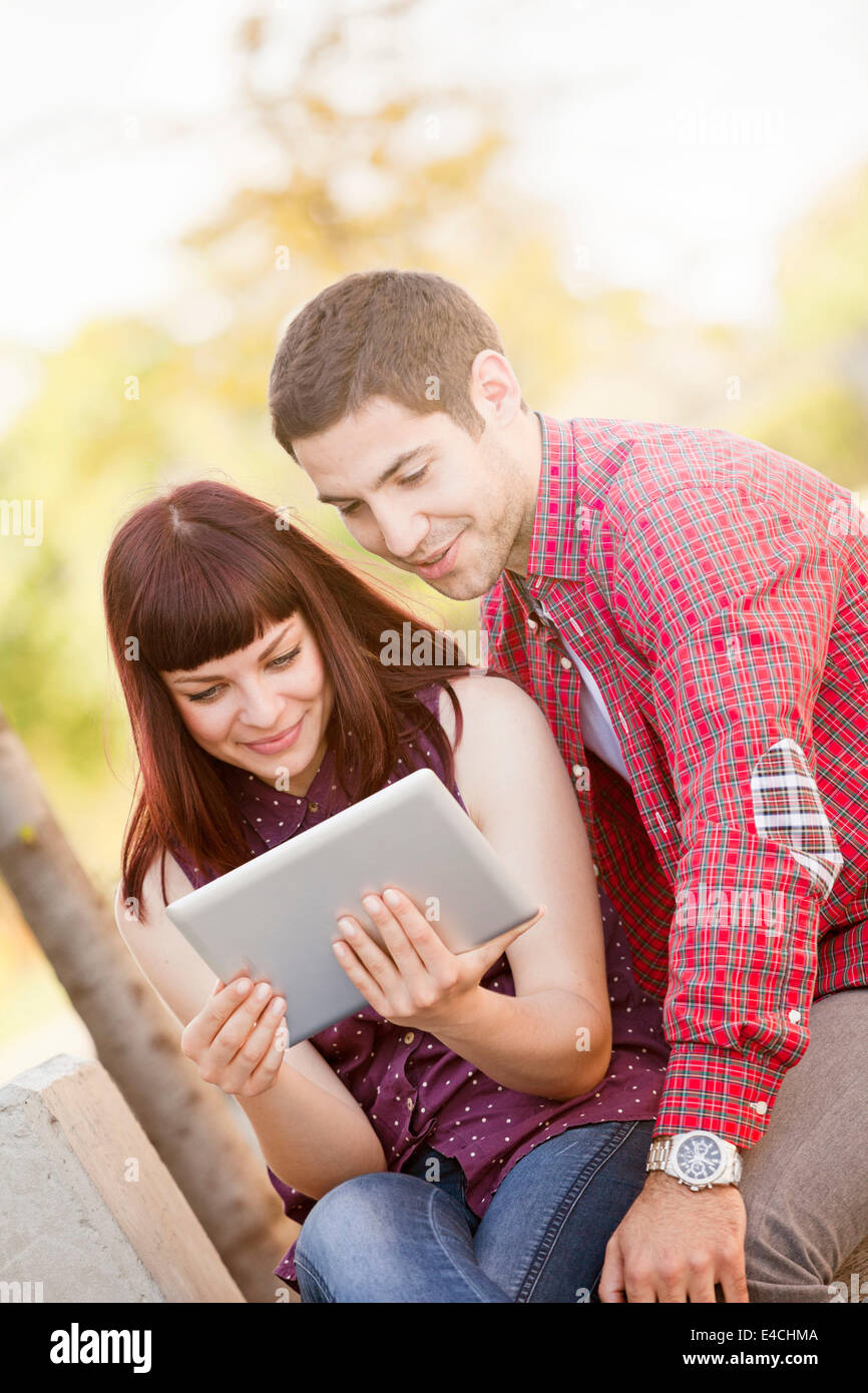 Young couple using digital tablet in sunlight, Osijek, Croatia - Stock Image