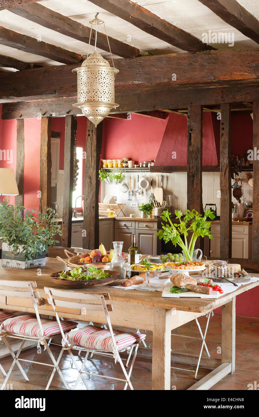 Laid table in large rustic French country kitchen with old ceiling beams Stock Photo