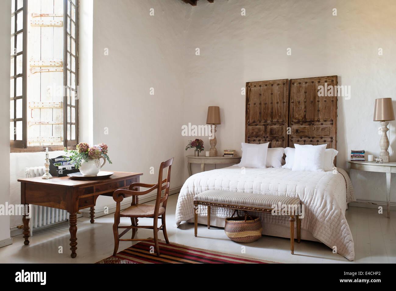 Pair Of Old Studded Doors Behind Bed In Spacious White Bedroom With Wooden Writing  Desk