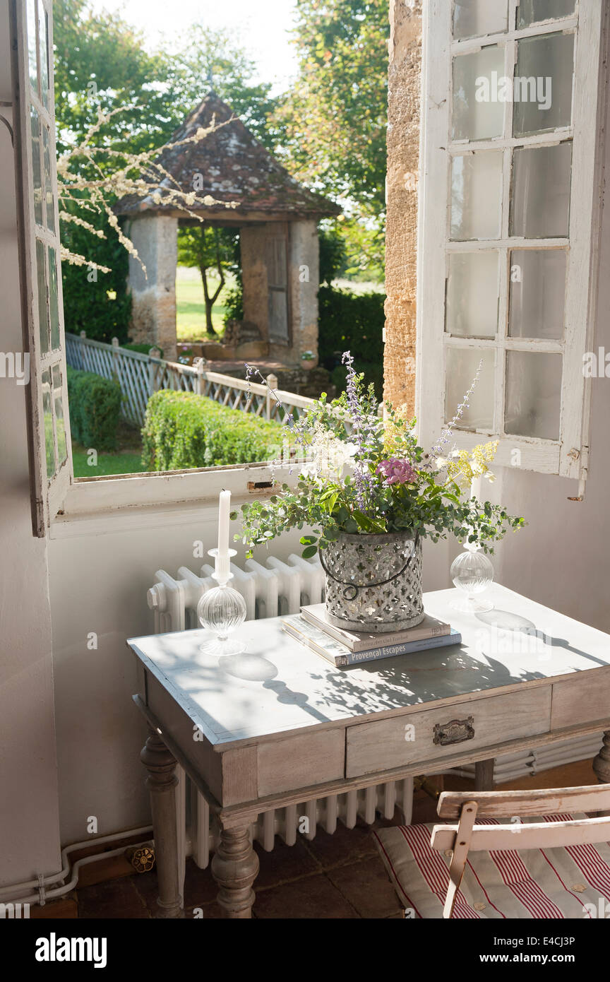 Small Wooden Writing Desk By Open Windows With View To Garden Stock