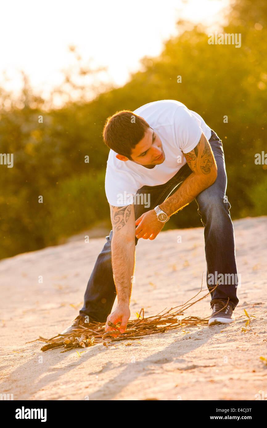Young man on riverbank gathering firewood, Osijek, Croatia - Stock Image