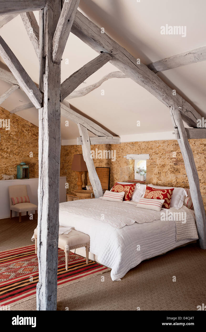 Exposed stone walls in attic bedroom with wooden ceiling beams and moroccan rug Stock Photo