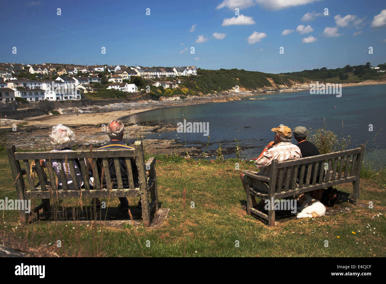 Cornwall. Roseland Peninsular. Portscatho. Two elderly couples sat on wooden benches. - Stock Image
