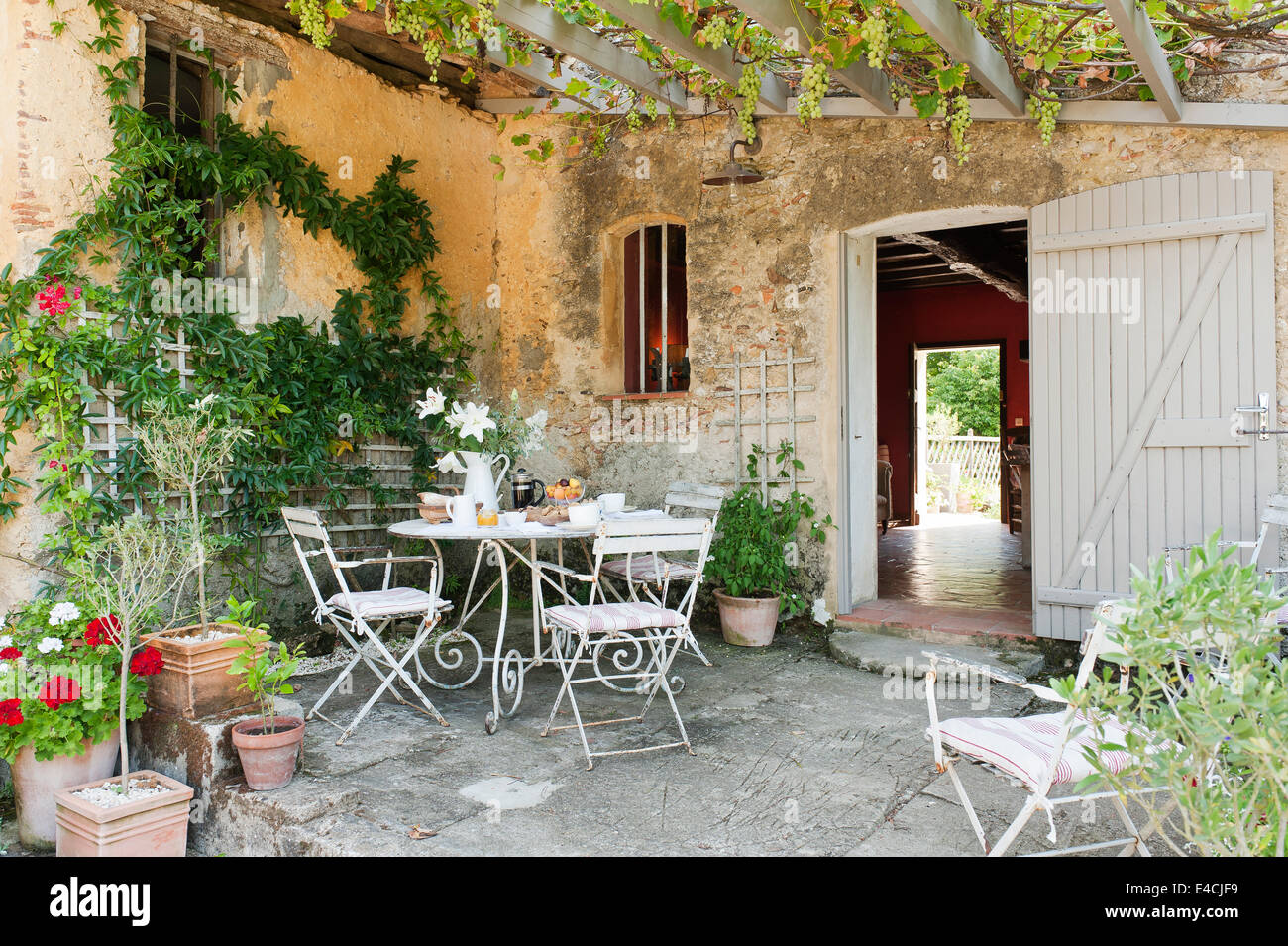 Wrought iron table and folding bistro chairs in courtyard with overhead trellis and grapevine - Stock Image
