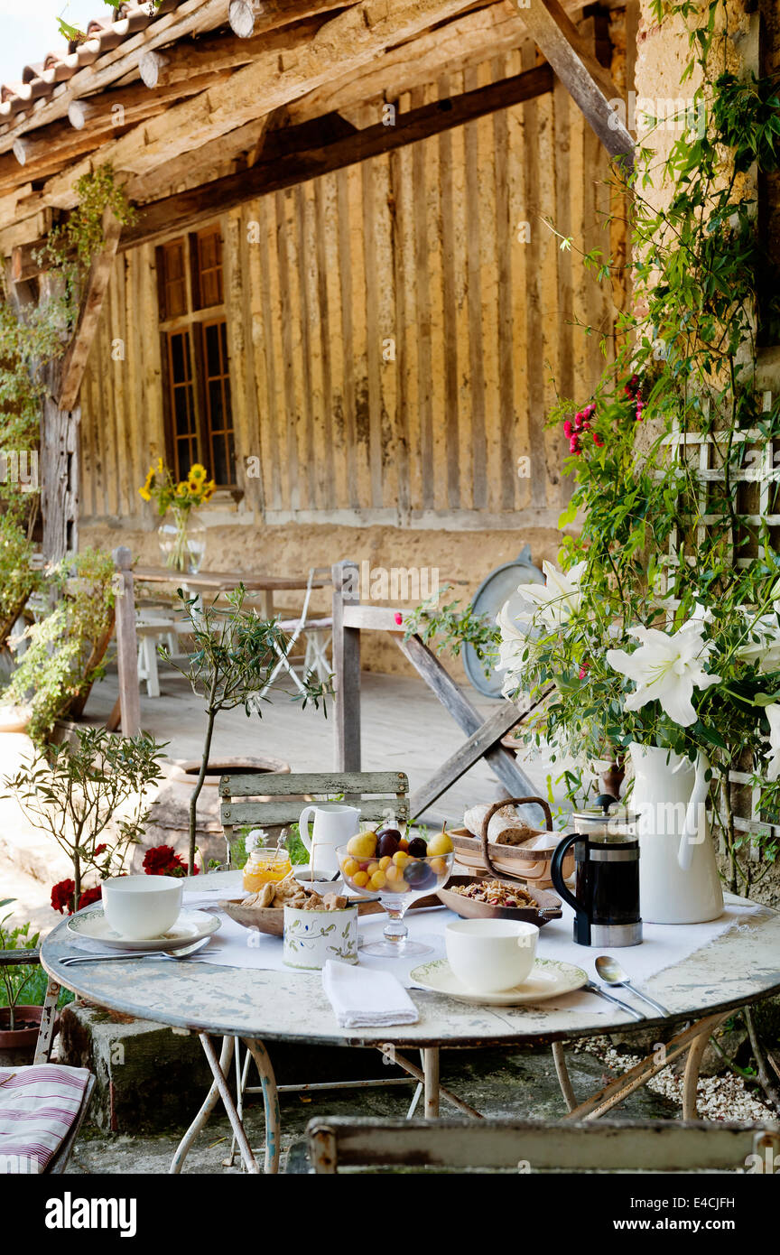 Breakfast laid on round table with folding bistro chairs in courtyard by old barn Stock Photo