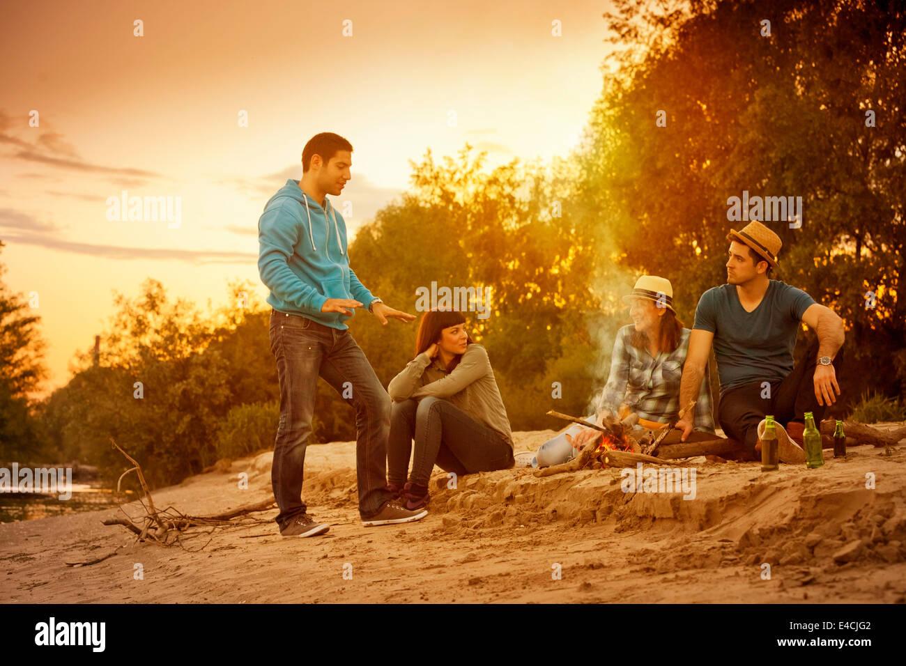 Group of friends talking by campfire, Osijek, Croatia - Stock Image