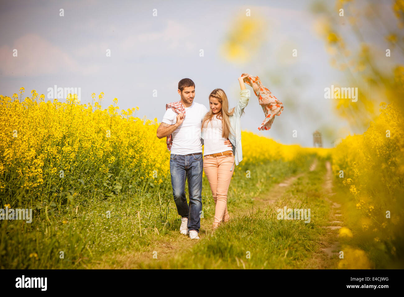 Young couple walking along field path by colza field, Tuscany, Italy - Stock Image