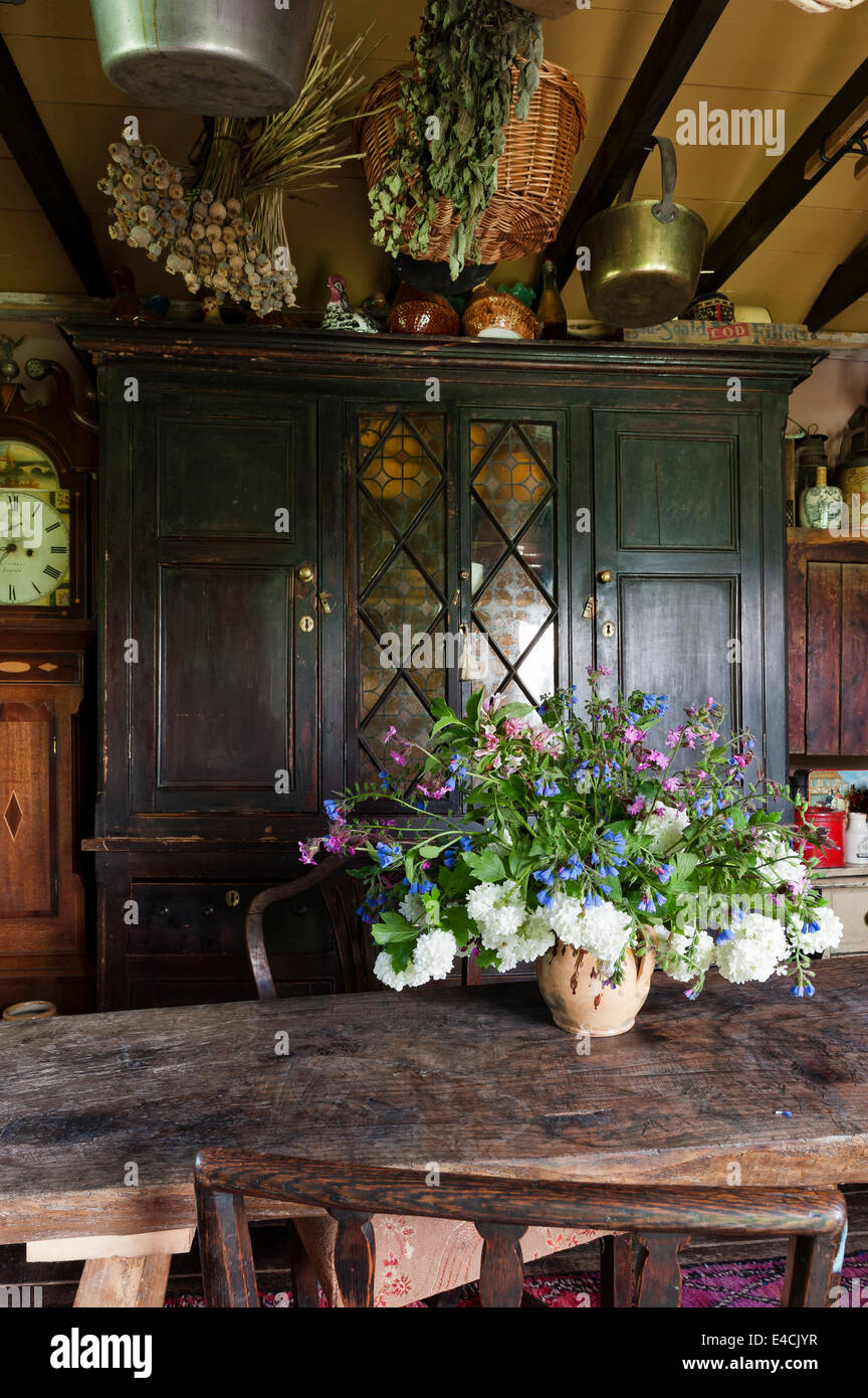Vase of flowers on narrow wooden table in country kitchen with old cabinet - Stock Image