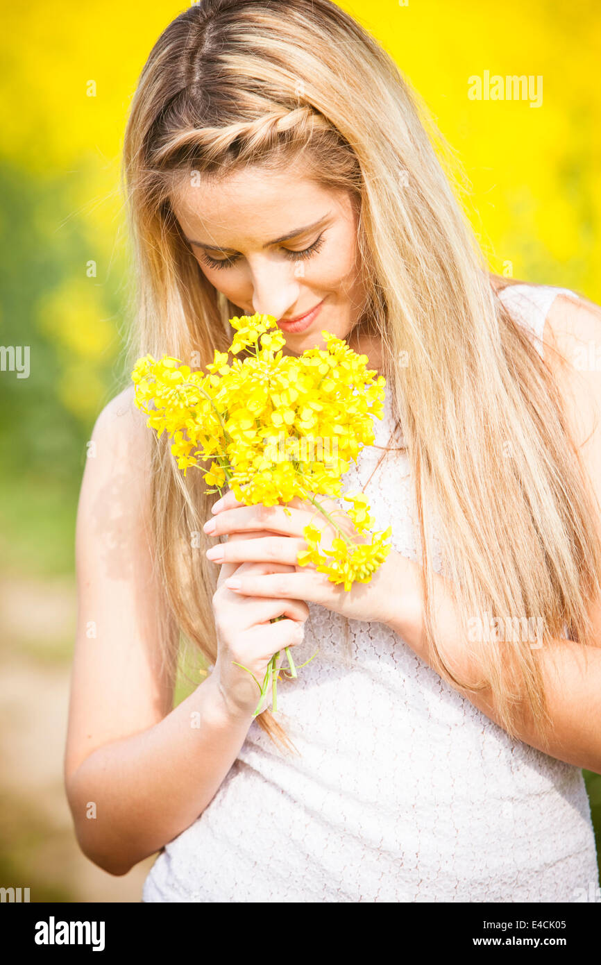 Young woman smelling colza flowers, Tuscany, Italy - Stock Image