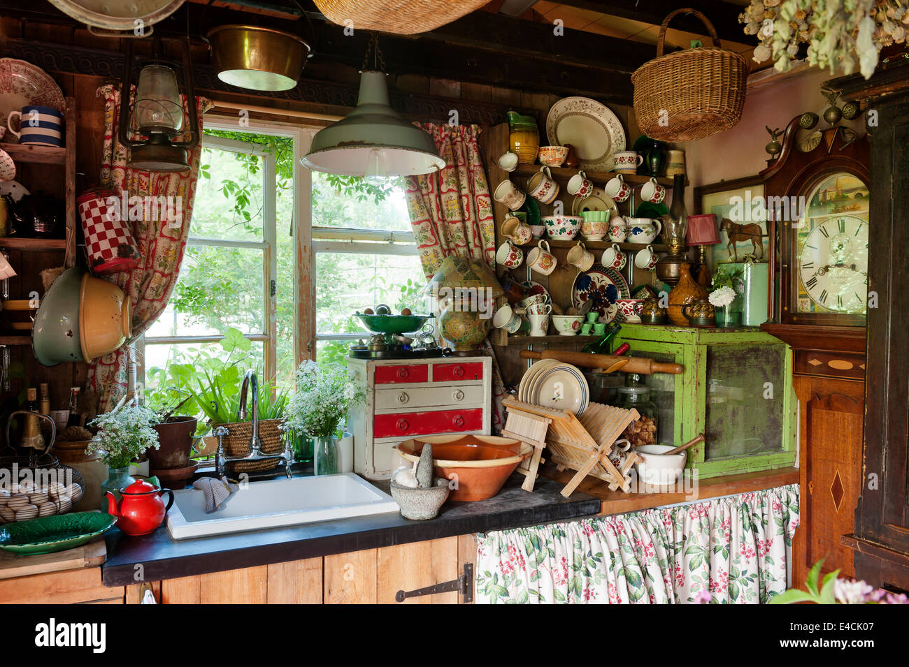 Sink area in shabby chic country kitchen with china adorning every surface and a grandfather clock in the corner - Stock Image