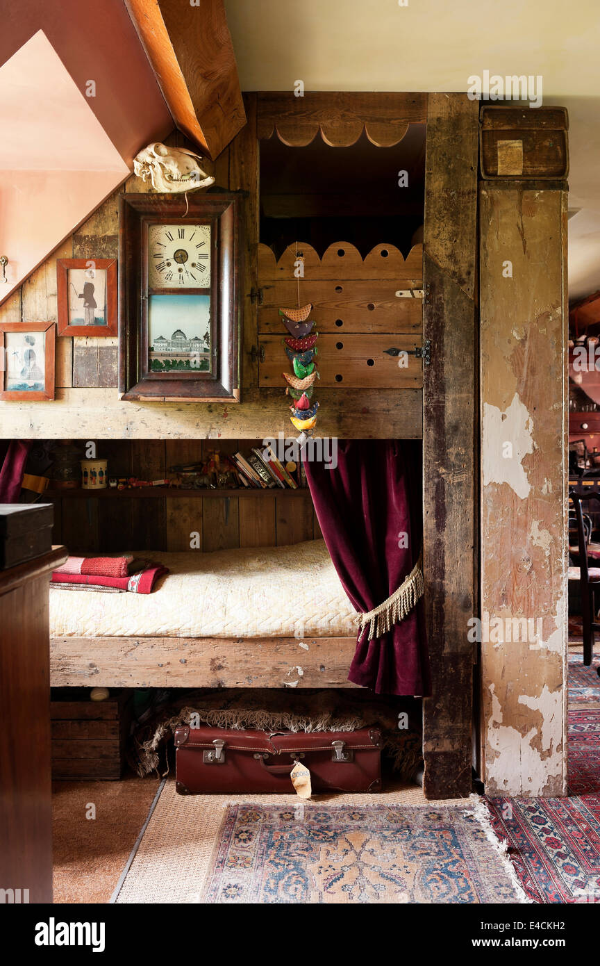 Bunkbeds made out of salvage wood with faded framed pictures and old clock - Stock Image