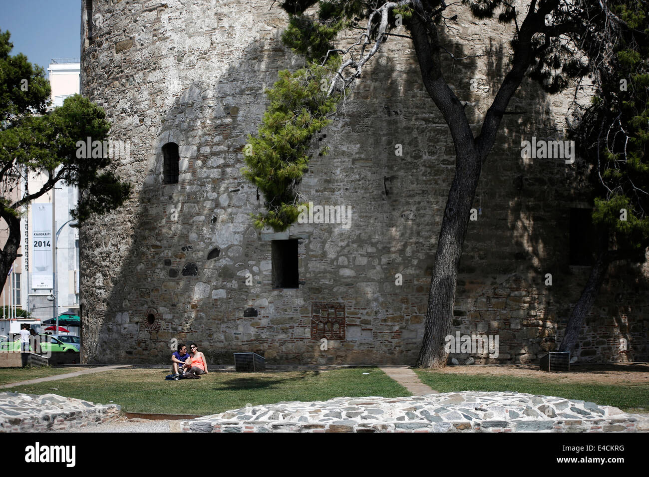 A couple relax under the landmark of Thessaloniki, the White Tower. Northern Greece - Stock Image