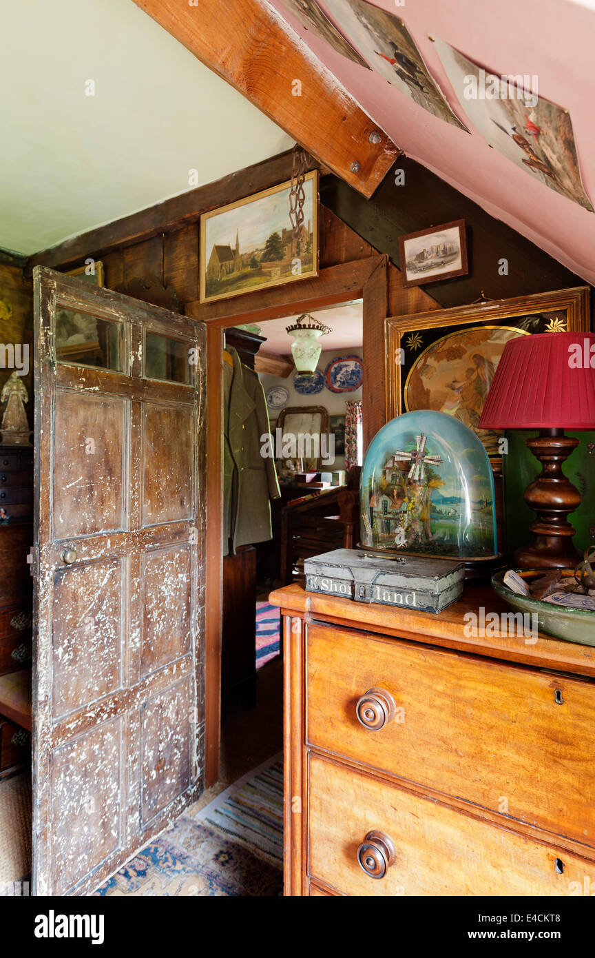 An Automaton musical windmill diorama on wooden chest in cluttered room with 17th century pine door - Stock Image