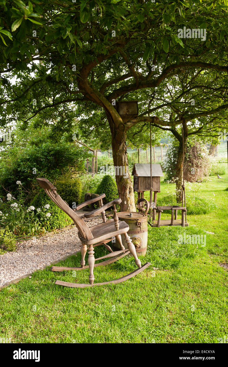 Wooden rocking chair and swing in garden of country cottage - Stock Image