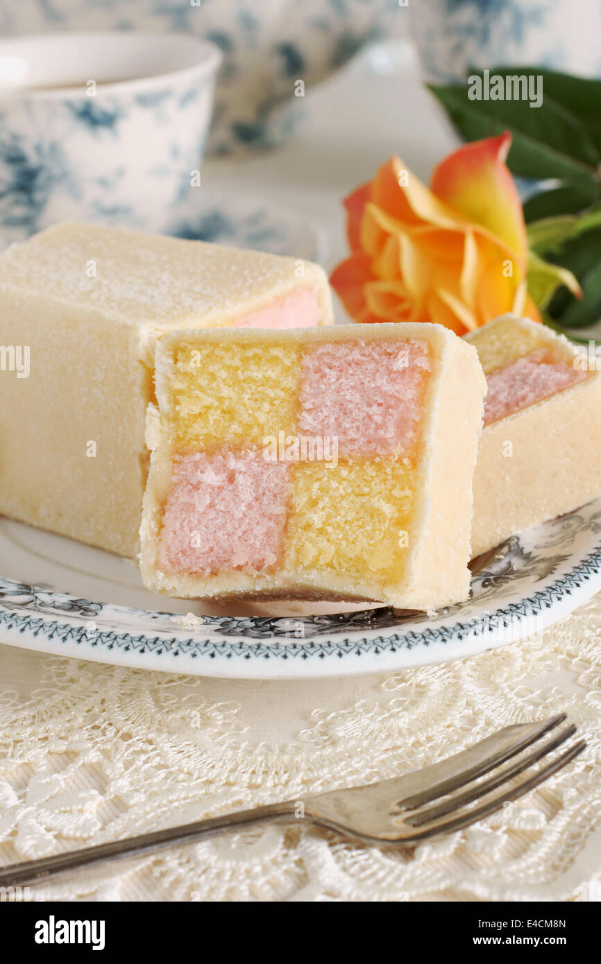 Battenberg Cake or Battenberg Square a sponge cake with pink a yellow checks covered in marzipan - Stock Image