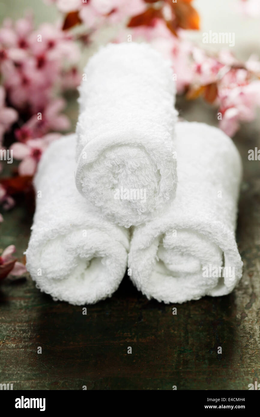 towels and spring cherry blossoms on wooden table - Stock Image